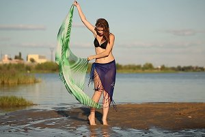 Girl dancing on river bank