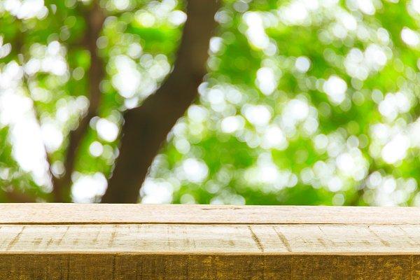 Wood table top on blur tree