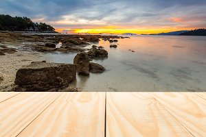 Wood table top on sunset beach