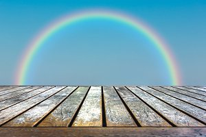 Wood table top on sky with rainbow