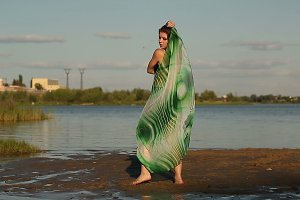 Girl dances on river bank