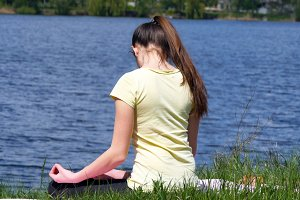 Young woman does exercises bends head to-and-fro. Girl sitting on the grass and meditate beside the river doing yoga exercises during lotus position