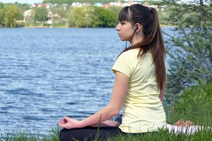 Young woman meditating and listening music on smartphone in headphones in lotus position. Girl sitting on the grass and relaxing meditating on the beach beside the river