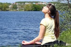Young woman removing his jacket enjoying sun and warmth. Girl sitting on the grass and relaxing meditating on the beach beside the river
