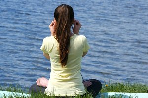 Young woman meditating and listening music in headphones in lotus position. Girl sitting on the grass and relaxing meditating on the beach beside the river