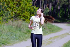 Girl running on forest path in a park and taking breath after jogging. Portrait of tired athlete woman resting, close up