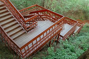 Circle red wooden stairs in the mountain forest.