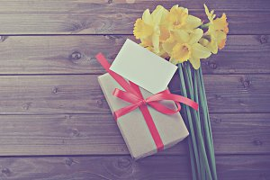 daffodils with gift box wooden table