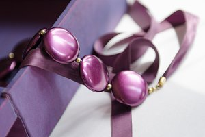 purple beads with ribbon on a white table overhang out of the box