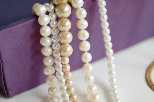 few beads of pearls hanging on a purple gift box necklace jewelry