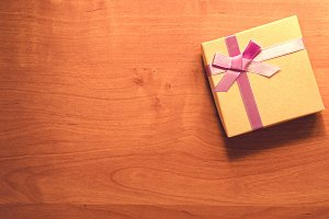 gift box with a bow on wooden table instagram filter