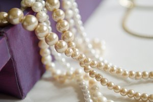 few beads of pearls hanging on a purple gift box