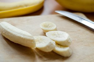 peeled banana sliced on cutting board with a knife