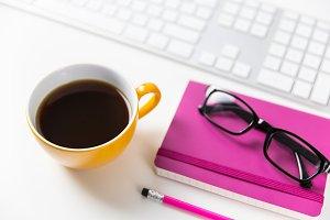Coffee, glasses + keyboard on desk