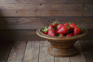 ripe strawberries in wooden bowl