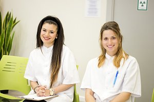 Two nurses smile at camera in hospital