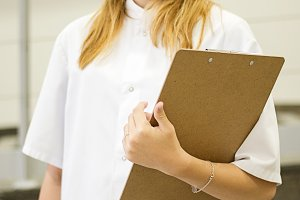 Nurse smiles looking at camera while holding a folder