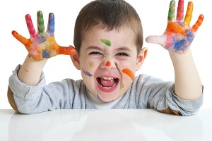 happy little boy with paints on hand
