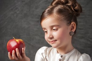 little girl holds red apple