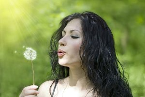 beautiful woman blowing dandelion