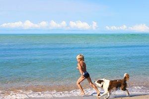 boy playing dog on sea