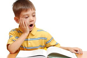 Boy reading book and yawning