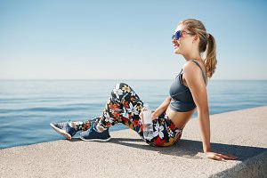 Young fitness blonde woman hold bottle water after fit at beach.