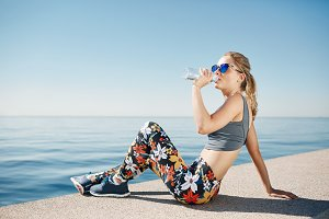 Young fitness blonde woman drinking water after running at beach