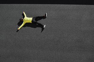 Top view runner in yellow sportswear resting lying on a black asphalt after running. Jogging man taking a break during training outdoors. Caucasian fitness model 20s in Barcelona, Spain.