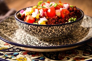 Quinoa with tomatoes chilli and corn on a plate with  black background pattern dark wood