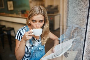 Casual closeup portrait of woman drinking coffee and reading mag