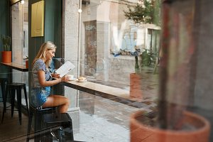 Cafe city lifestyle woman sitting in trendy urban cafe reading m