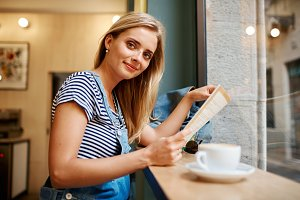 Portrait of a young pregnant girl who is sitting in a cafe readi