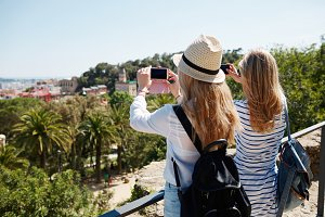 Couple tourists taking photo landscape with camera phone on park