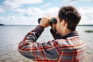 Close up back portrait man looks through binoculars while fishin