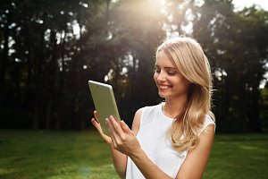 Closeup portrait of happy young blonde woman using tablet pc in