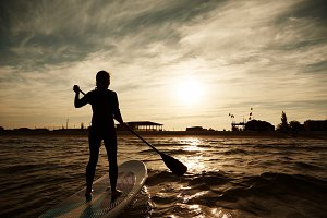 silhouette of young girl paddleboarding at sunset, recreation sport paddling ocean beach surf orange sunlight reflection hue on water.