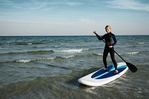 Young blonde female paddles a paddleboard at the sea .