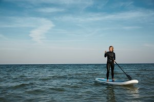 Young blonde female paddles a paddleboard at the sea.