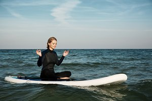 Stand up paddle board yoga performed by beautiful girl on the bright sunset background, yoga training on the beach.
