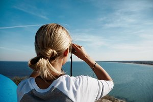 young beautiful woman hiker looking through binocular on mountain in summer.