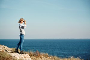 Woman tourist looking through binoculars at distant sea, enjoying landscape, copy space
