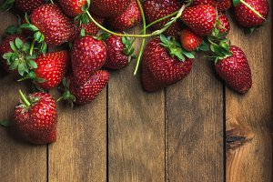 Strawberries over natural wooden background
