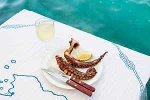 Grilled octopus and white wine glass