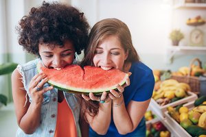Two young woman eating watermelon