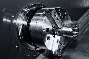 black and white rotating brilliant part of an automated lathe for machining of metal parts