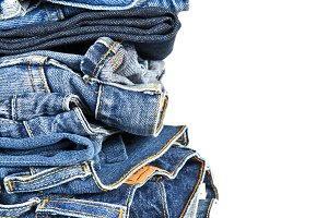 Stack of blue jeans over a white background