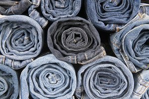 Rolls of different worn blue jeans stacked