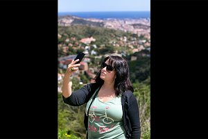 Black haired woman taking selfie