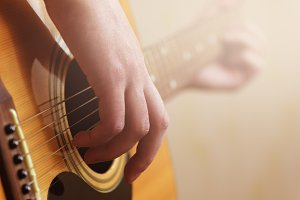 hand playing on acoustic guitar